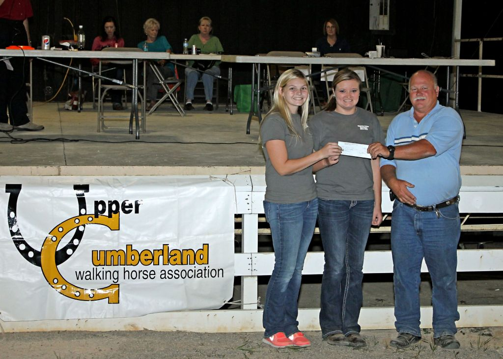 Gary Stidham, UCWHA Show Manager, presents check to Dekalb FFA members Jackie Overbey, Chapter President and Rayanna Baker, Chapter Secretary.